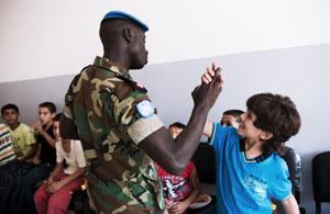 Un enfant libanais et un casque bleu ghanéen à l'inauguration de la salle informatique. photo : Juliette Robert/Youpress