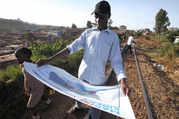 Frederick Bary et la carte des bureaux de vote de l'ONG Map Kibera. © Martin Vanden Bossche