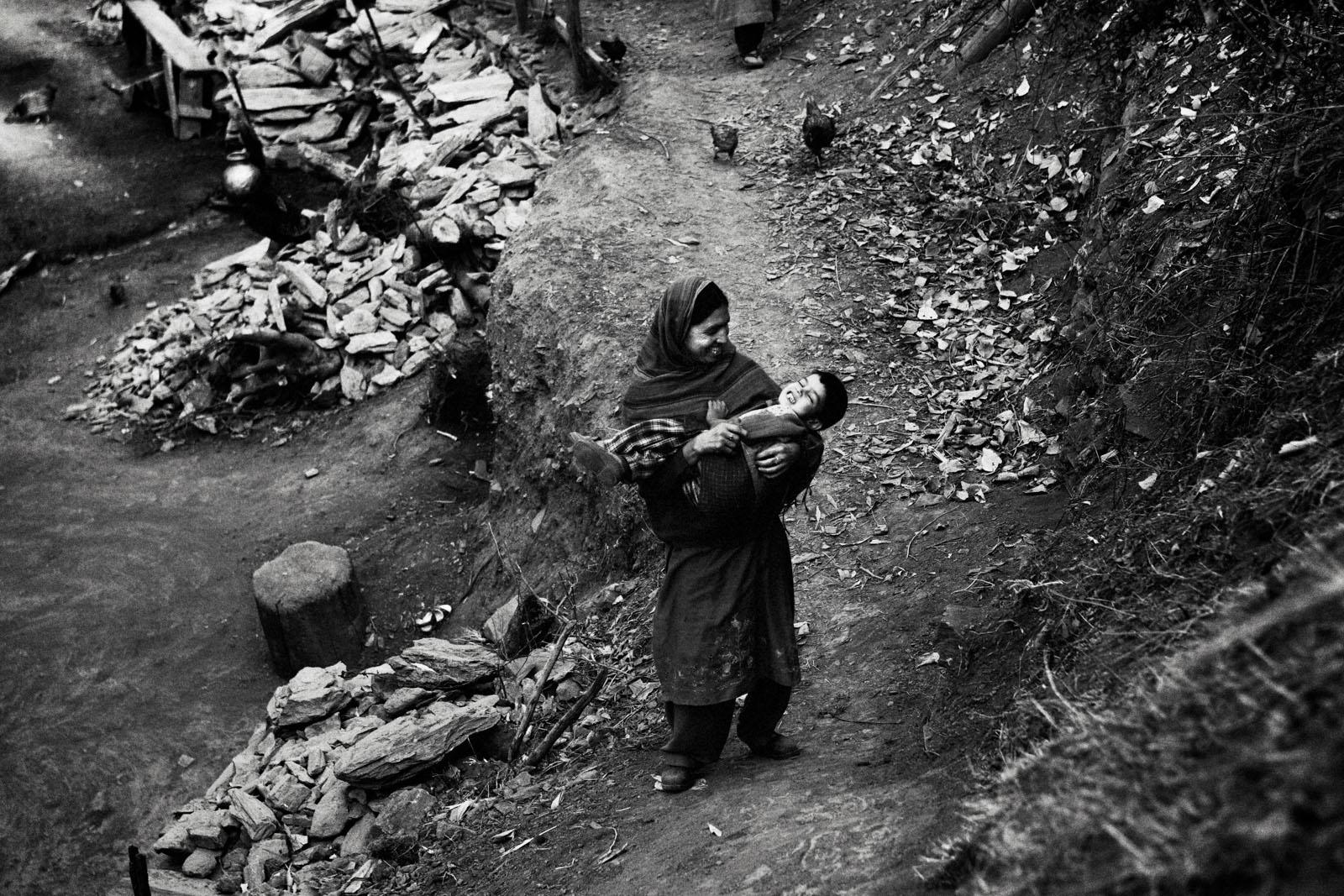 A women plays with her boy in Khudhalem, north Kashmir