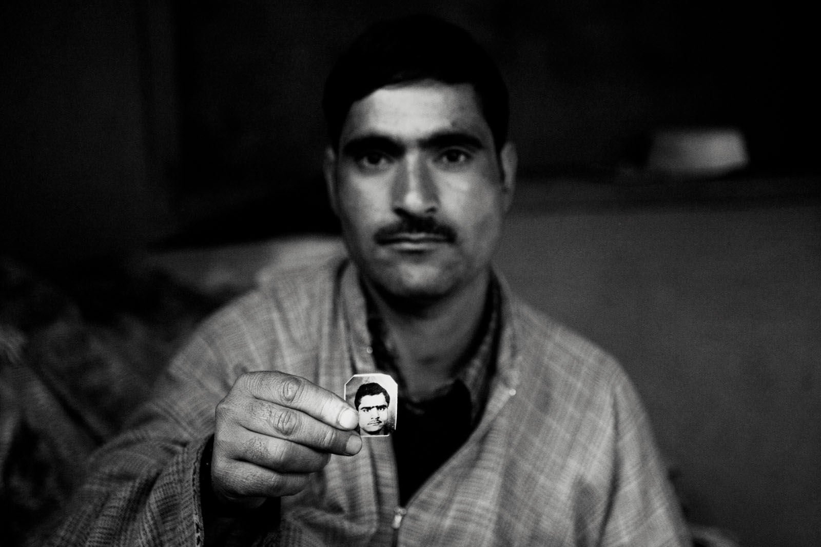A man shows the picture of his missing brother, in north Kashmir