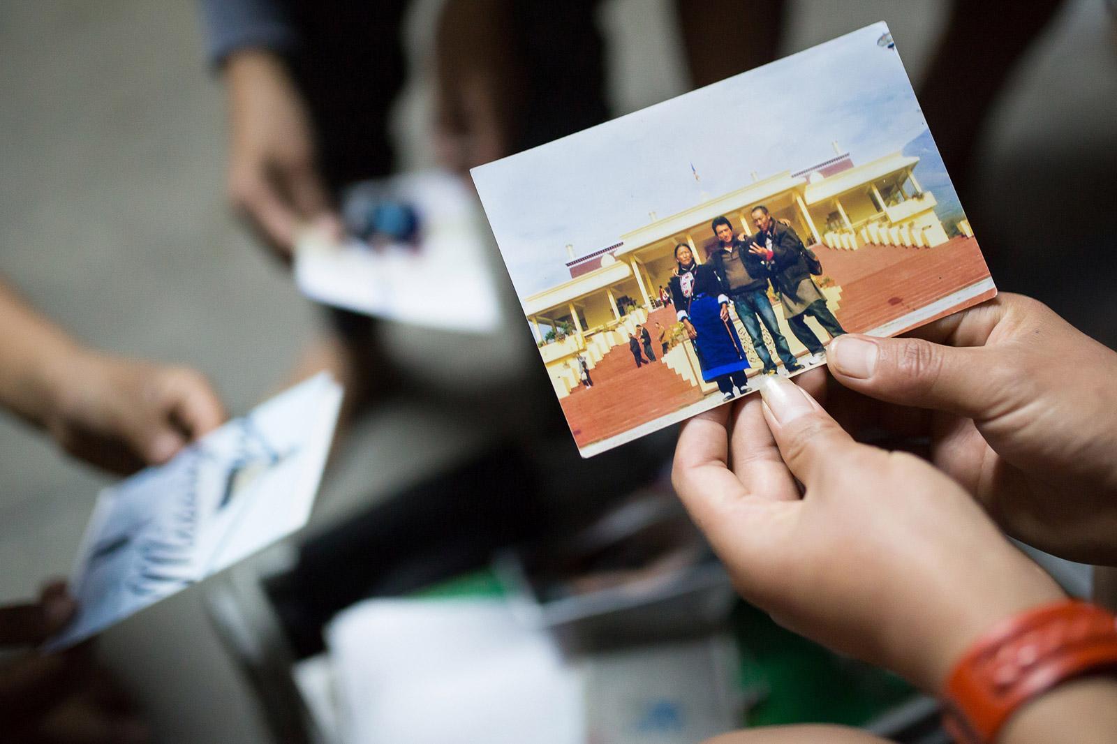 Un enfant regarde une photo de sa famille, restée au Tibet. 90