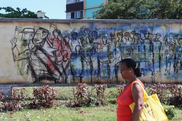 Une habitante de Santiago de Cuba passe devant une fresque à la gloire de Fidel Castro © David Breger