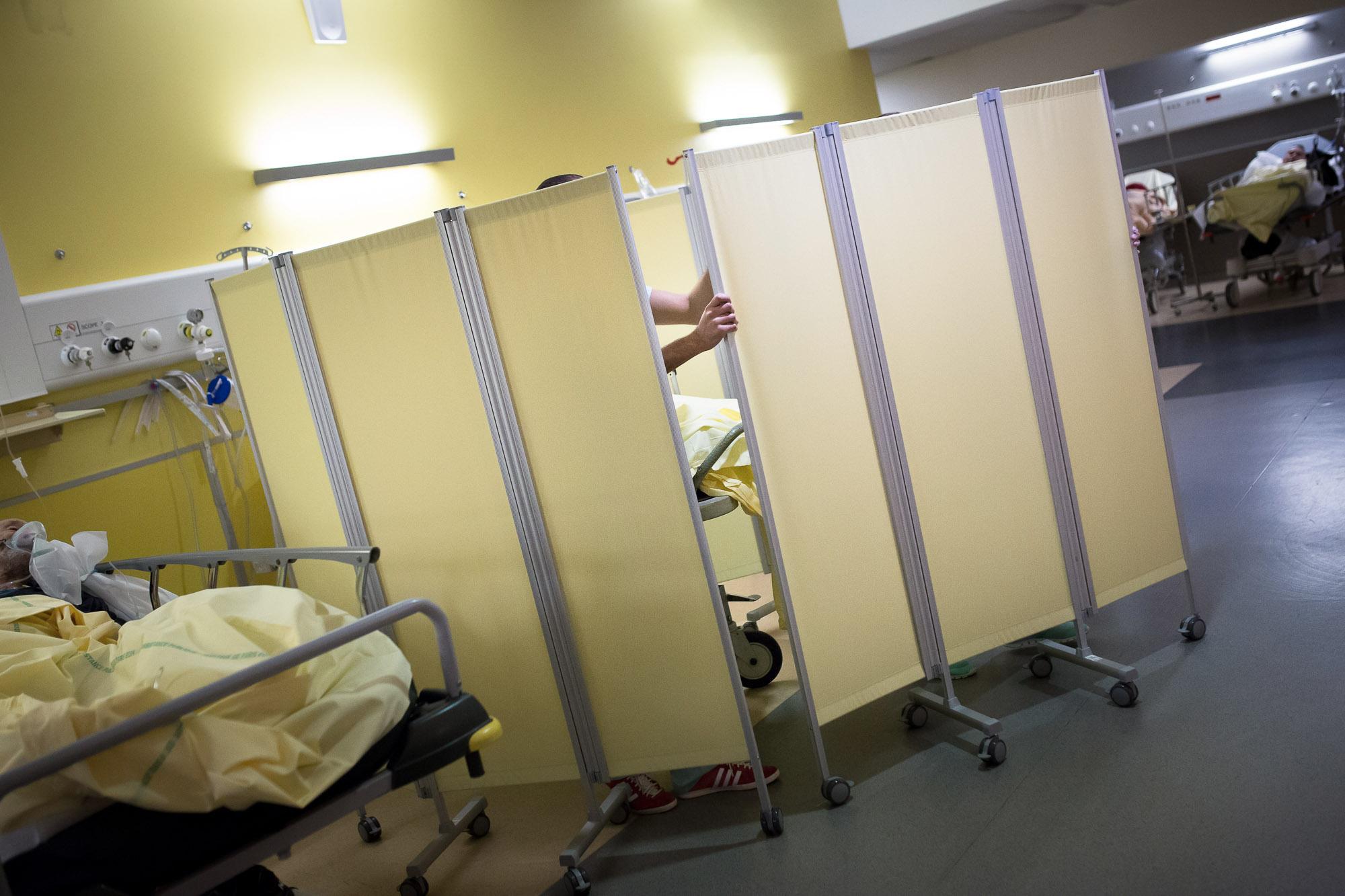 Un aide-soignant installe des paravents autour du lit d'un patie