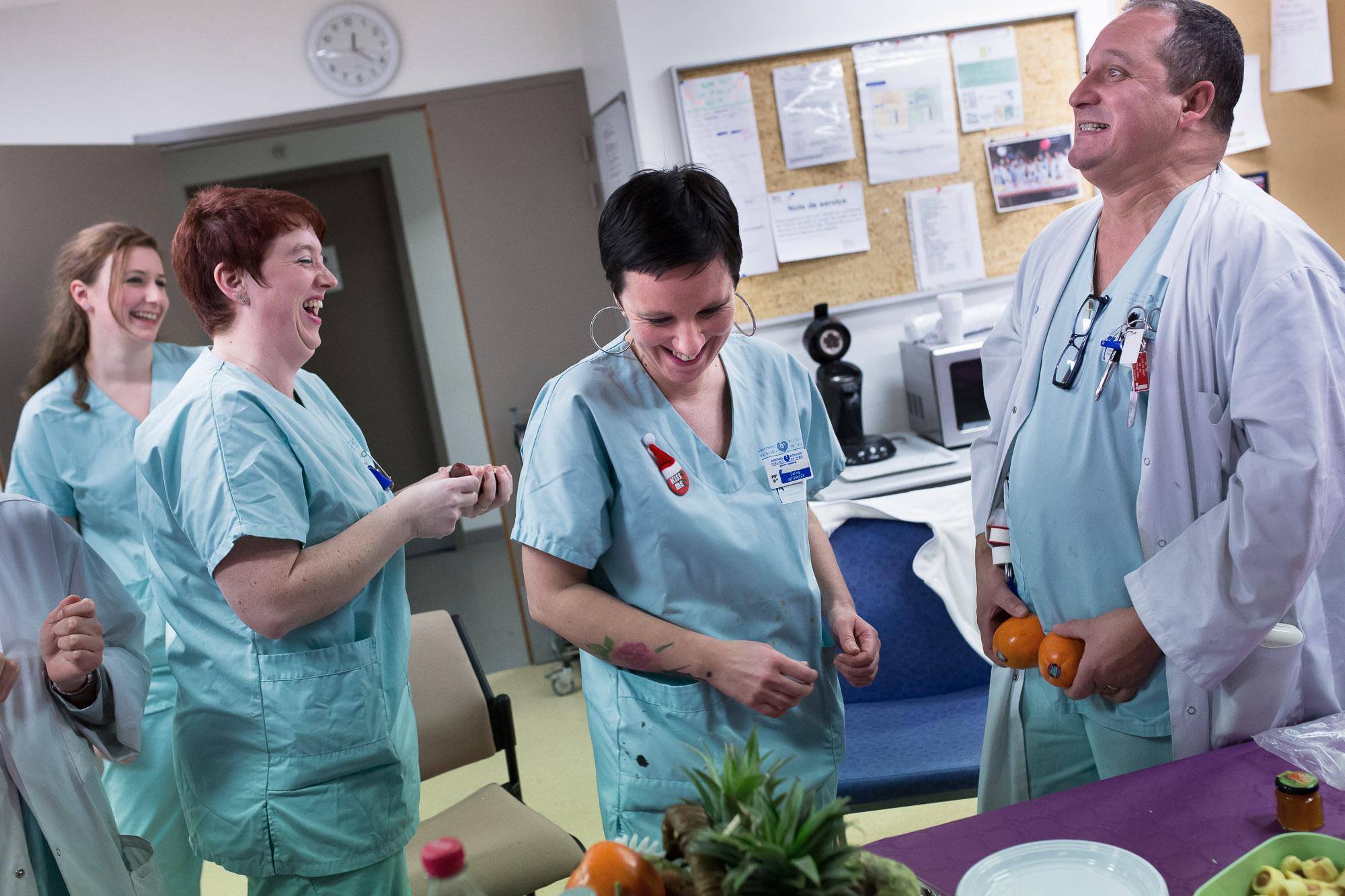 Un aide-soignant fait rire ses collègues en salle de détente.