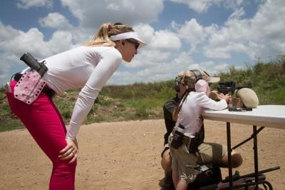 Niki la fondatrice du club de tir feminin Sure Shots observe le pere de la plus jeune membre des mini sure shots agee de 4 ans en train de l'aider a tirer au pistolet. ©Moland Fengkov/Haytham-REA